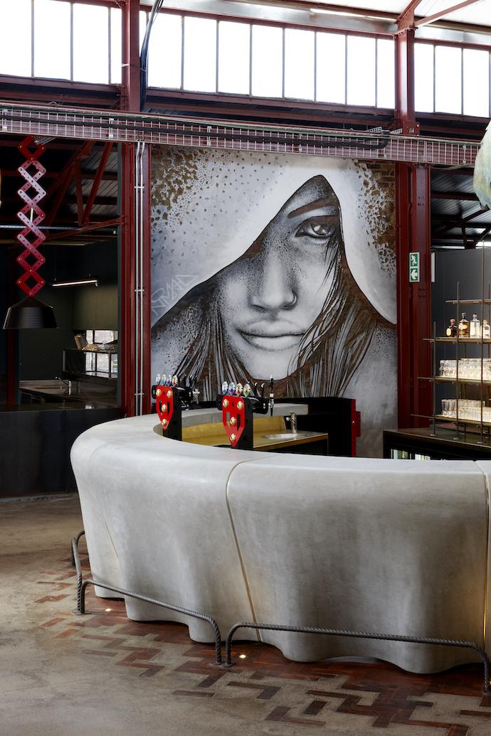 The walls of the brewery feature works by graffiti artist Nomad. The cast-concrete bar counter, which is 6 m in diameter, takes the form of a giant bottle cap.