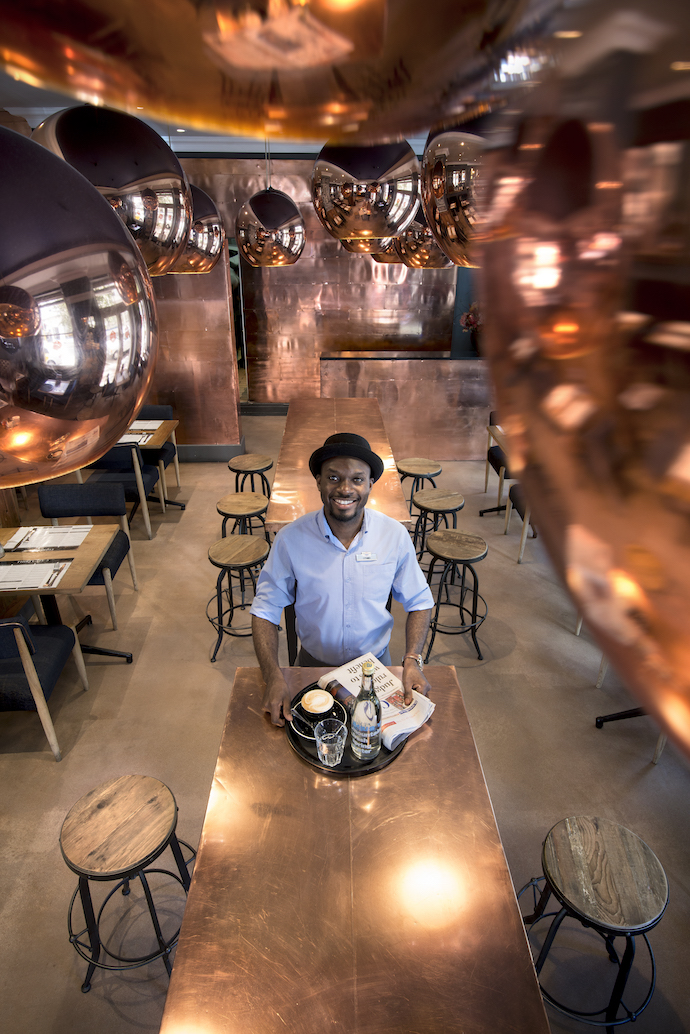 Luthando Ncube gets into the lunchtime swing of things. Copper rules throughout the hotel, in tune with the Tom Dixon copper pendant lamps.