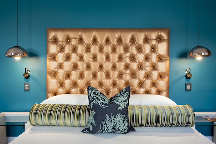 One of the superior rooms, by Beachhouse Interiors, is all dressed up in peacock blue, accentuating the dramatic gold headboard, a feature in all the rooms.