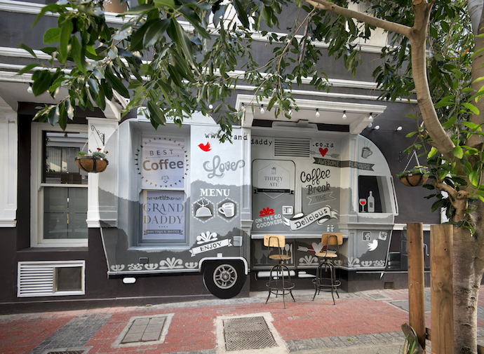 """Grab a coffee through the hatch of the delightful """"food truck"""" outside, an airstream trailer designed by Leanne Munckton and painted by Courtelle from Catch Media."""