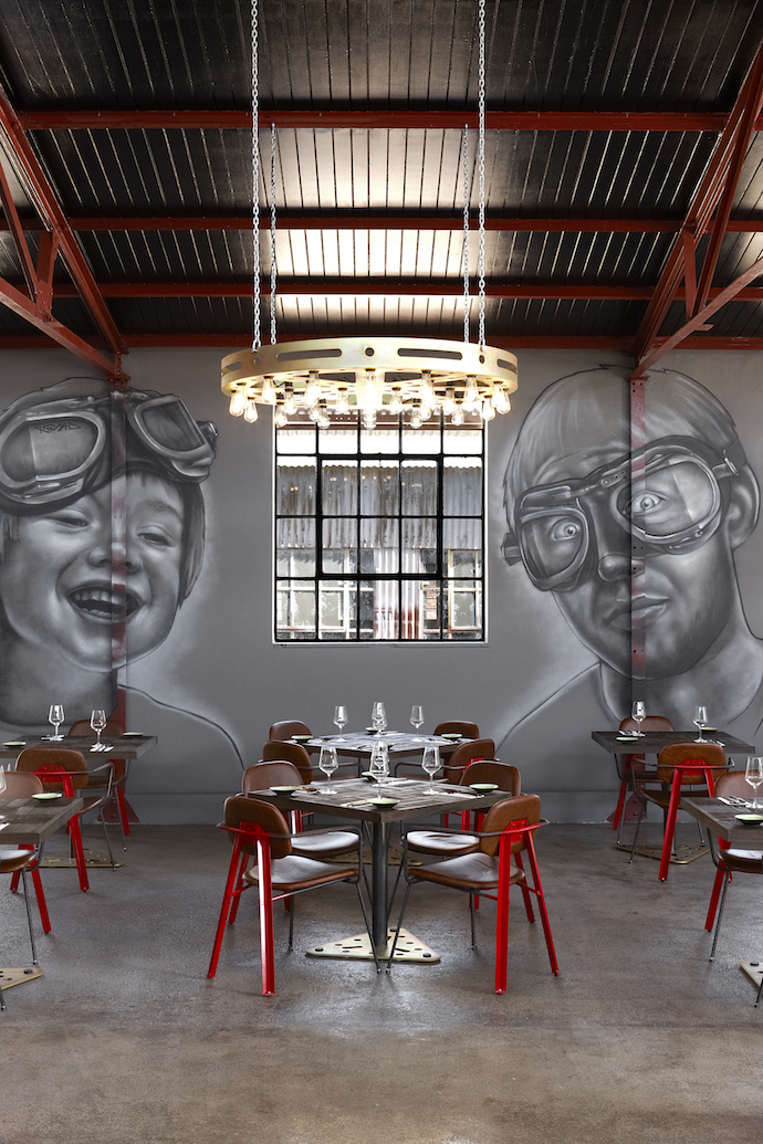 The dining chairs have rebar arms and legs, metal back and legs sprayed bright red with a Mad Giant emblem laser-cut into the back, and seats and seatbacks upholstered in distressed leather with red stitching. On the wall is another greyscale mural by graffiti artist Nomad.