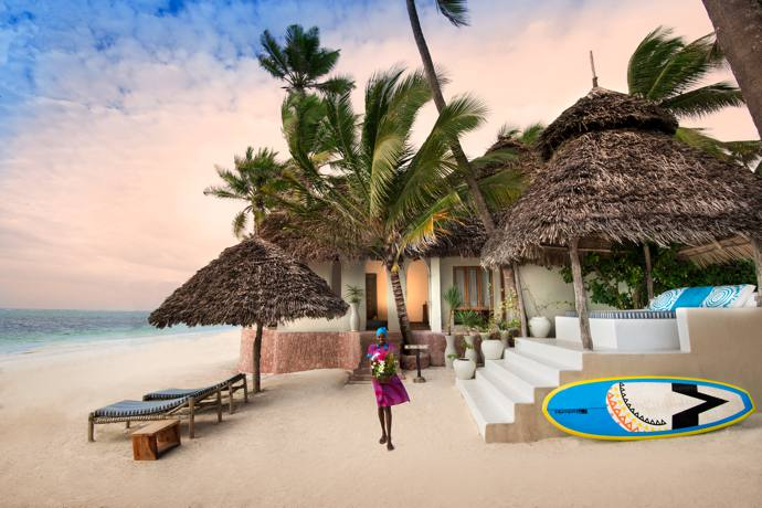Mary Ndongo carries a floral bouquet down to the pristine beach. Take your pick from the activities on offer: Get pampered in the spa, order coconut cocktails and laze on the beach, go for a dip or take part in one of the various water sports on offer.
