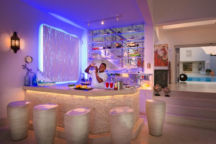 Segio shakes a martini at the bar with its festive lighting in the villa.