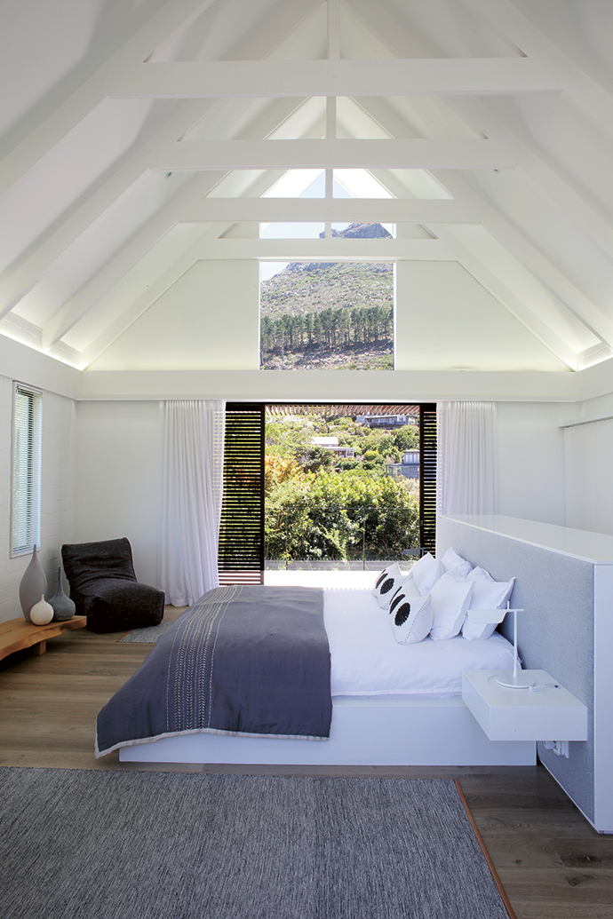 The white exposed beams of the living area are repeated in the master bedroom with its matching triangular window in the eaves that lets the mountain in. The sliding door opens to the garden, pool and entertainment area. Concealed lighting on dimmers allow for warm, soft light. The chairin the corner, sourced in Australia, is a Koskela Quadrant Soft.