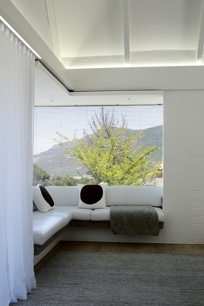 The glass-encased L-shaped window seat in the master bedroom has beautiful, unending views towards the bay.