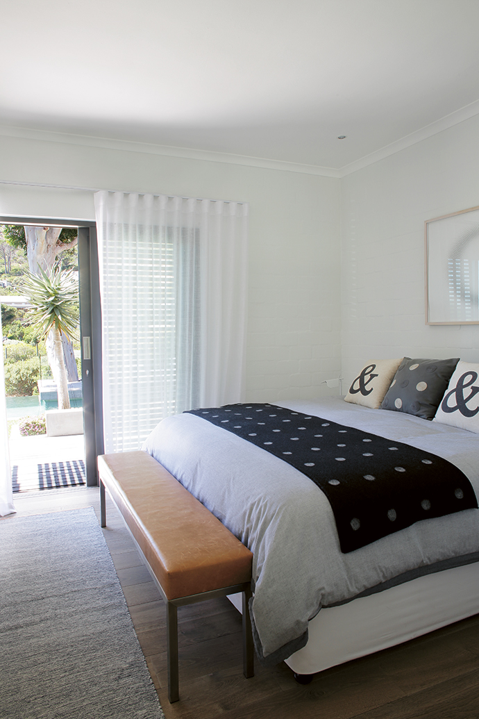 Sliding doors with shutters open the guest bedroom to the garden. The bed linen is from Woolworths and the cushions are from NAP Living.