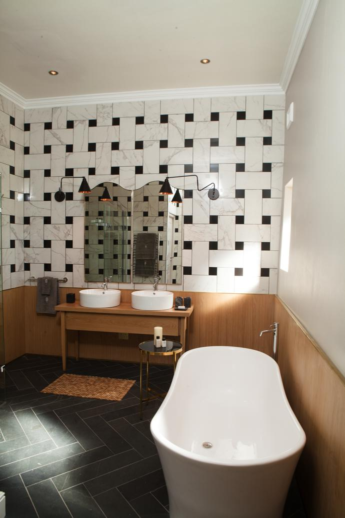 Liam designed the basket-weave tiling layout in this bathroom to reference a riempie chair. Black and white tiles from Italtile were cut to size. He also designed the gabled brass mirrors and the oak vanity.