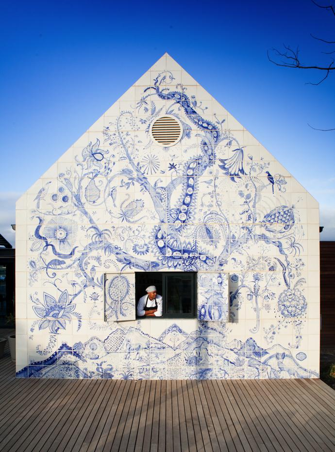 Chef Victor Phillips looks out of the window in the wall of the restaurant that features a blue-and-white tiled mural, the Bosjes Tree of Life, created by Lucie de Moyencourt and Michael Chandler.