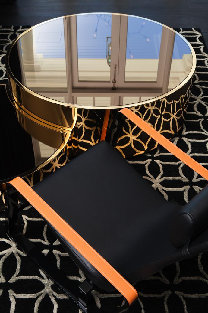 In the formal lounge, a mirrored Constellation coffee table by Fendi Casa is flanked by a Cité armchair by French designer Jean Prouvé. The graphic rug is from Gonsenhausers Fine Rugs.