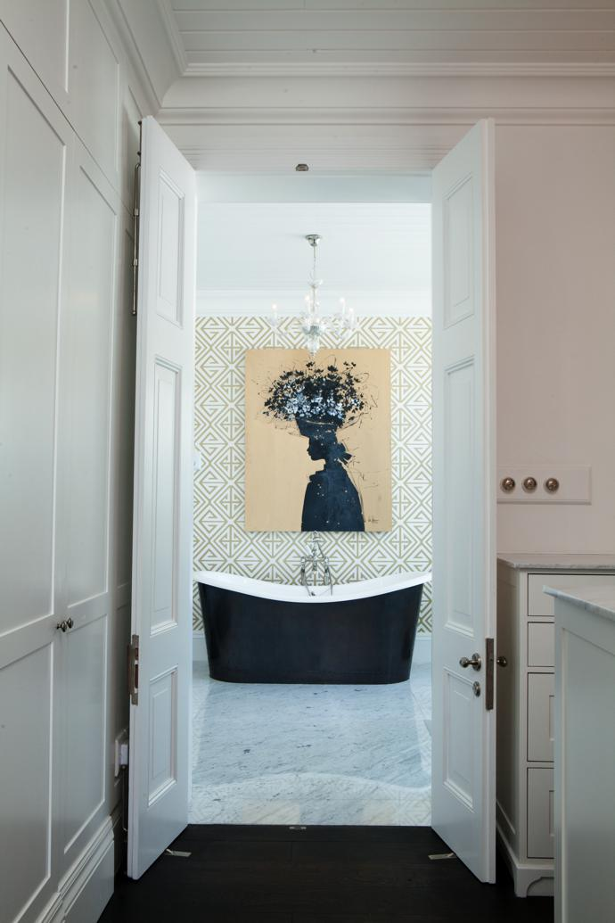 The master bedroom's en-suite leads off the walk in wardrobe. An Abe Opperman painting, Harvest, hangs above the double slipper bath. The sanitary ware is all by the luxury British manufacturer Lefroy Brooks.