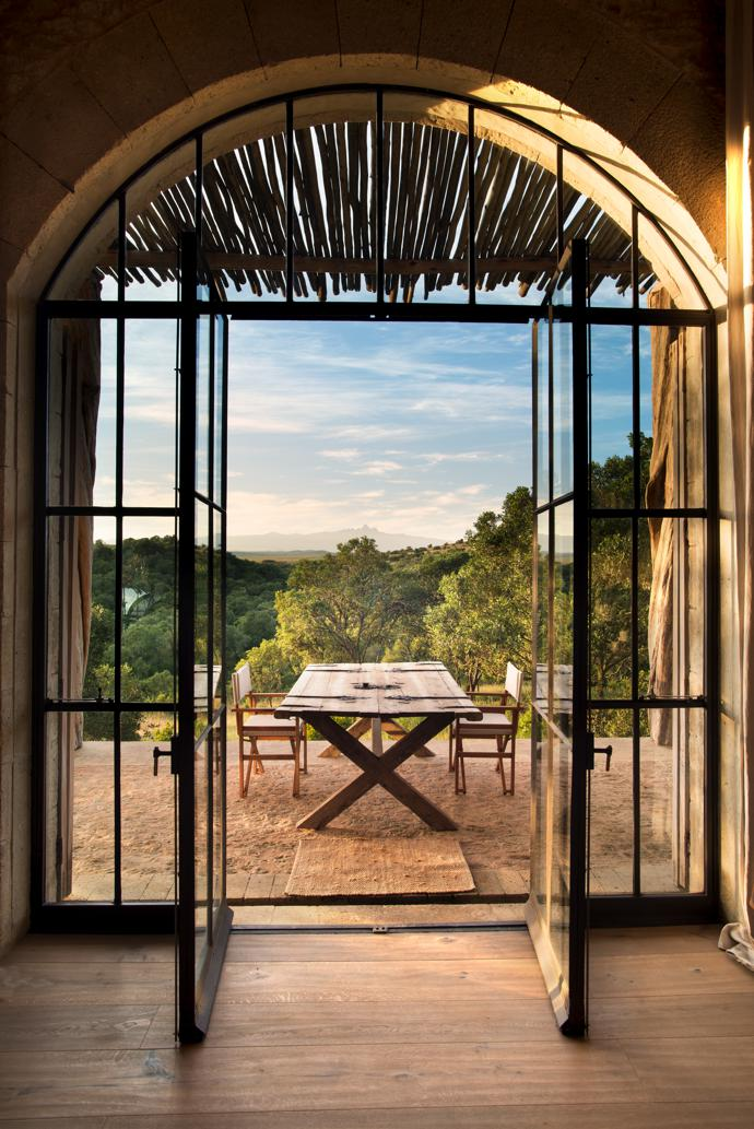 The most breathtaking of breakfast views. Rough-hewn floors pick up the morning light as a rustic reclaimed-door table and simple safari chairs invite guests to enjoy the endlessness of the Arijiju wide open world.