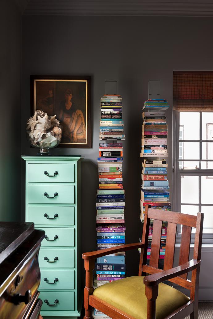 "In the library nook is a chest of drawers that was repainted to give it new life, a chair that used to belong to an aunt of Lesley's that was reupholstered by Astrid, neat vertical shelving for books, and a print of a Moses Soyer painting of a dancer that reminds Lesley of her aunt. ""Even the shells have been in the family forever."""