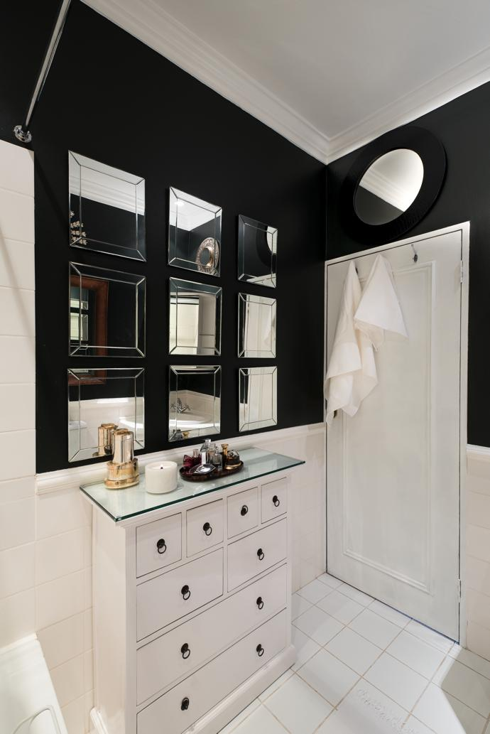 The tiny bathroom works hard to create space with mirrors on the walls, a repainted chest with extra drawers and a nifty overhead rail where washing can be hung above the bath on wet days.