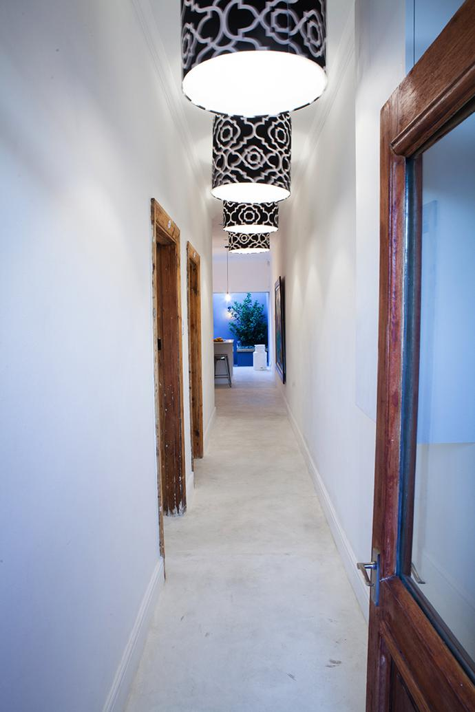 An all-white hallway is lit by custom-made pendant lights with black-and-white shades made by Ivy White Productions with fabric from Constantia Fabrics.