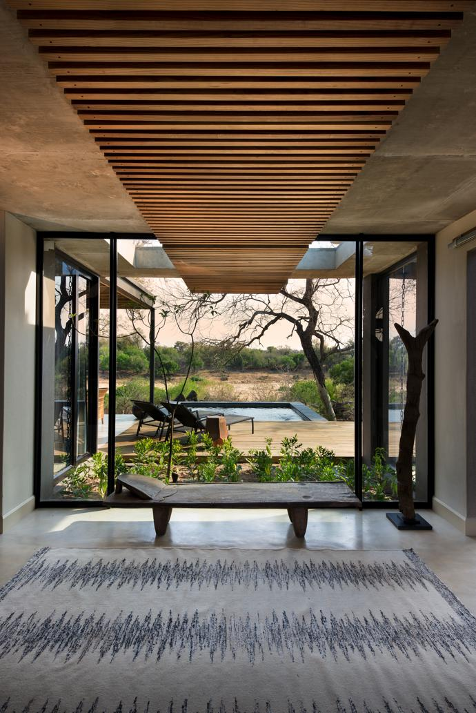 Large picture windows in the villa entrances connect guests to the outdoors with views of the veld beyond the swimming pool. The shepherd's bench is from Amatuli and the rug is from Hertex