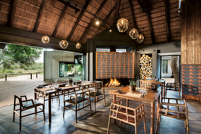 The dining area reflects the lodge's focus on privacy, giving guests the options of smaller tables and booth seats. The tables and chairs were made by David Krynauw and the pendant lights were made by Greencraft Lighting.