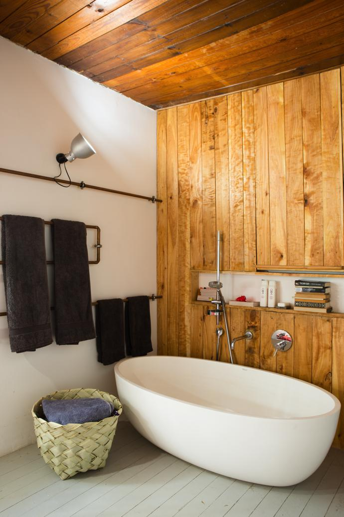 The homely bathroom, which is part of the bedroom, features a contemporary tub from Builders Warehouse. The towel rails, by Kevin Fellingham Architects, are also the water pipes that carry the hot water from the solar heating unit.