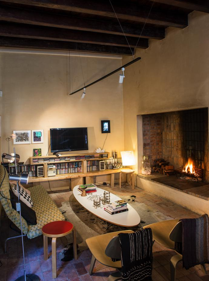 The lounge features an Eames coffee table and chairs, side tables by Alvar Aalto for Artek, a '60s standing lamp by Peter Nelson, an Akari YA2 table lamp by Isamu Noguchi, and a large fireplace.