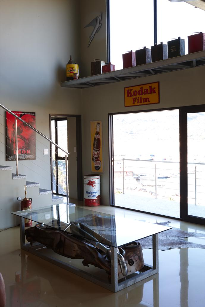 The living room features a coffee table made from a 1953 Ford front end, which Dieter found in the Karoo. A collection of vintage 2-gallon oil cans is displayed on a high shelf.
