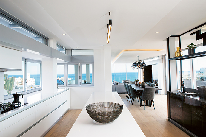 The bar provides storage behind elegant tinted glass doors. The upper steel frame keeps the structure light and maximises the views. A Little People rectangular lamp hangs above the custom-made eight-seater Kappa dining table, which links the kitchen and the living area.