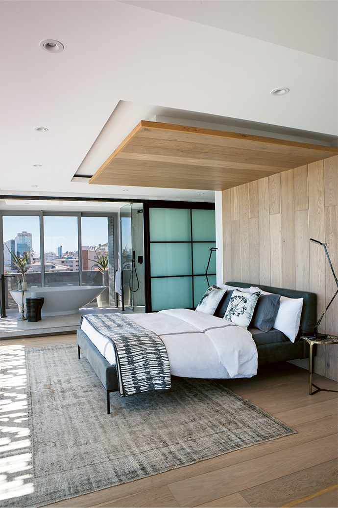 "In the master bedroom, the custom-made Oslo bed sits centrally in front of an oak wall-and-ceiling panel. Raised ""wings"" on opposite ends of the room house the dressing room and lounge on the one side and the bathroom on the other side, separated by glass sliding screens."
