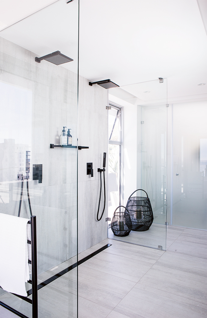 The master bedroom's en suite has grey tiles, matte black taps and an asymmetrical bath. All the bathrooms and the scullery have underfloor heating.