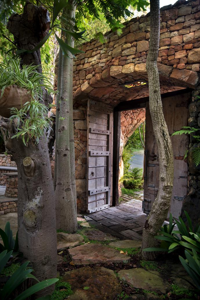 Entering through these majestic wooden doors from the street, you find yourself in an organic paradise that reveals its secrets step by manmade step.