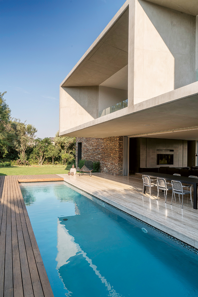 The long, narrow swimming pool mirrors the proportions of the house. Alongside the pool are Vico Magistretti Thonet-inspired Silver chairs, chosen for their lightness of form.