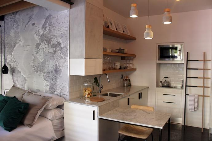 Wallpaper featuring a world map, digitally printed by ArtLab in Woodstock, denotes Ruhan's love of travel. The kitchen wall cupboard has an Earthcote Pandomo resin-based stucco finish in a colour called Skaapvel. That and a trio of concrete pendant lights from @home introduce a raw, textured element.