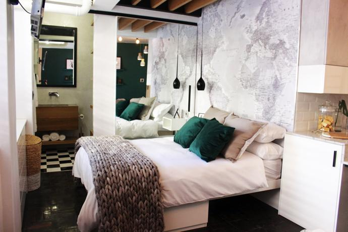 A large mirrored sliding door, which cleverly doubles as a door for both the wardrobe and bathroom, also serves to create the illusion of depth, making the room appear bigger than it is. The black pendant light used as a bedside lamp is a space saver. A hand-made grey merino-and mohair throw from Krafthaus in Somerset West, velveteen cushions from Hertex and bedlinen from Fabric Centre add texture and timeless appeal. Chequered tiles in the bathroom and a taupe basket give it a colonial touch.