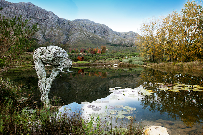 "The view of the lake Dylan shaped, with Stellenbosch Mountain as backdrop. The face of the stooping Male Trans-Figure III is obscured. ""It puts a focus on the body as a vehicle for expression as opposed to the face,"" says Dylan."