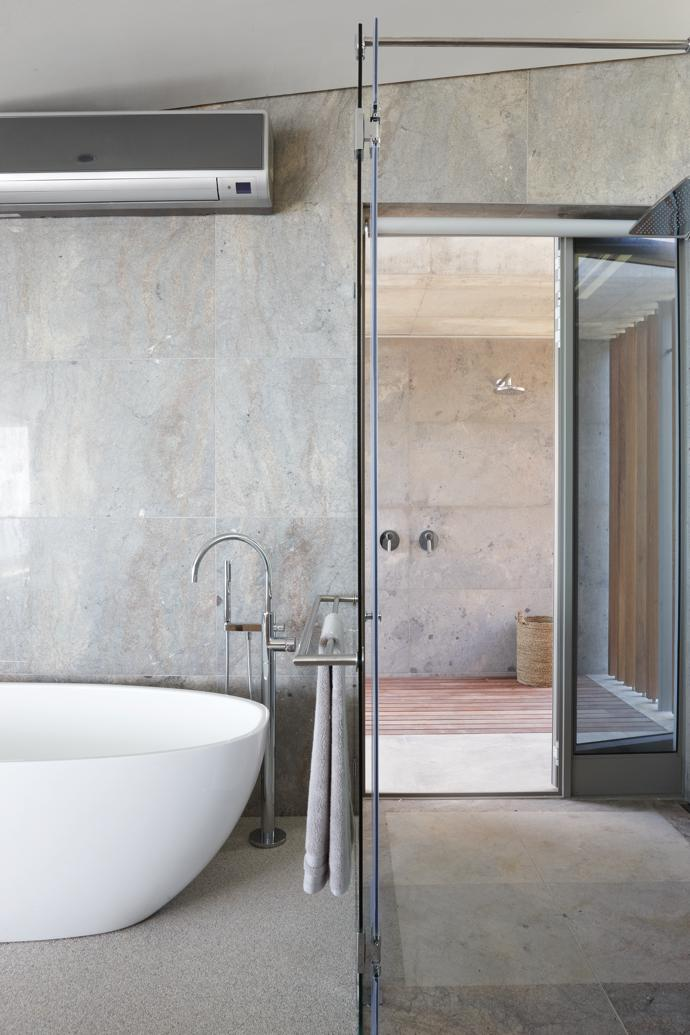 The en-suite bathroom is kept minimal, with the bathtub providing another unique vantage point to enjoy the view from.