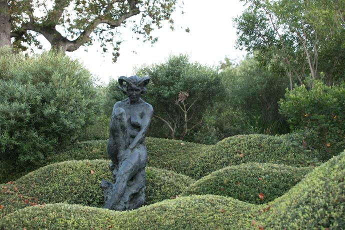 "A female form, Trans-Figure XXII, among undulating, meticulously pruned shrubs. ""The paradox of the garden does not escape me: that for someone who dearly loves the wilderness I have attempted to control, contract, constrain."""
