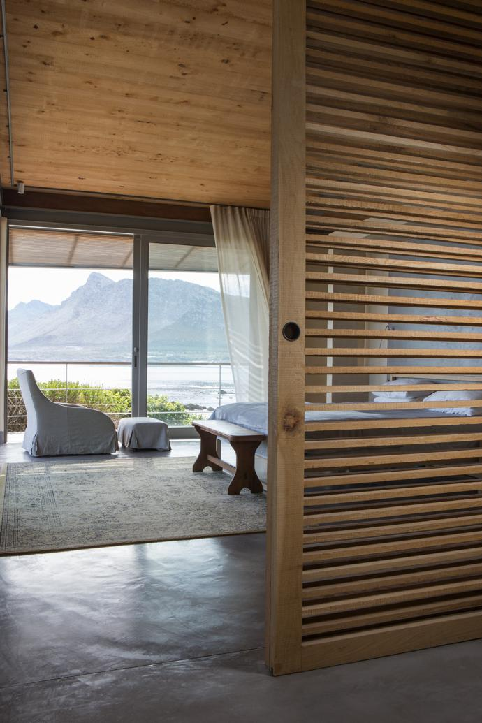 In the spacious main bedroom, slatted oak sliding screens by Jonathan Cooper can be drawn closed for privacy. The furniture is from Weylandts.