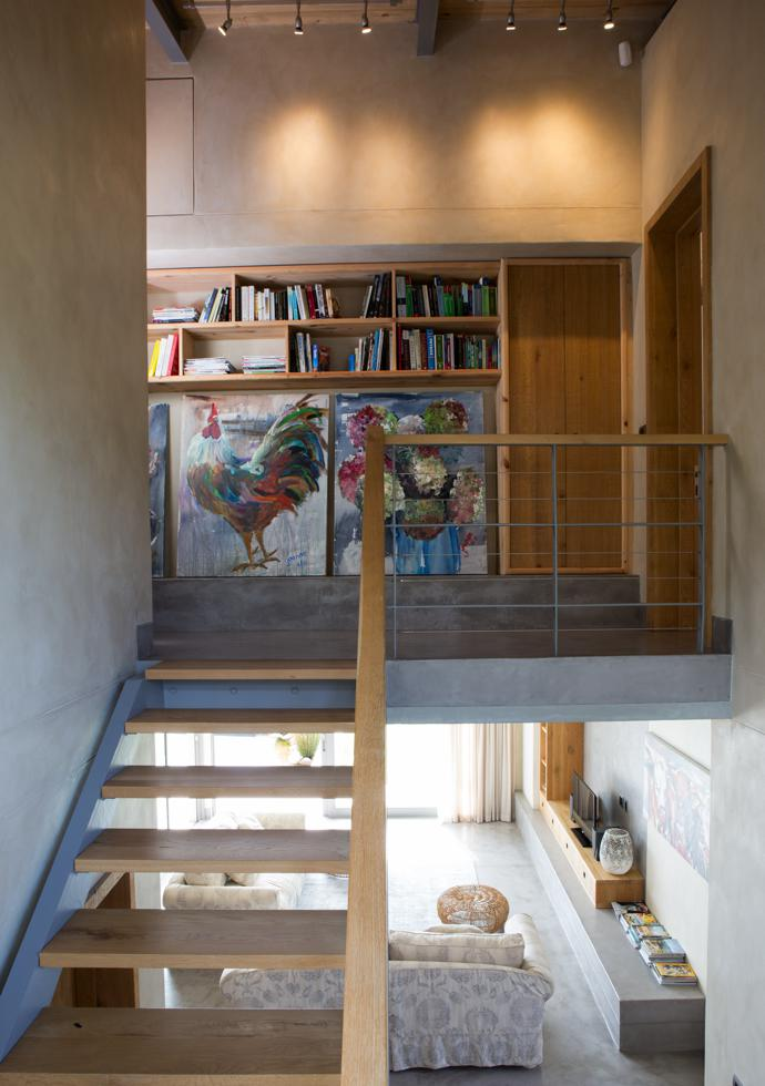 A floating steel-and-timber staircase leads to bedrooms upstairs. The two paintings are by Jeanne Alston from Montagu.