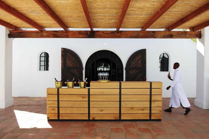 The outside tasting deck with its timeless earthtoned terracotta tiles. The terrace is furnished with a rustic-chic oak bar by Laurie Wiid van Heerden of Wiid Design, on top of which the estate's signature bubblies await visitors.