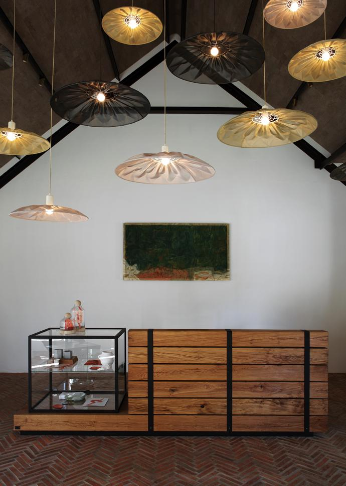 In the arrival area, striking Ukhamba fan lamps by Mema Designs are suspended above an oak-and-glass counter by Laurie Wiid van Heerden of Wiid Design, who also made boards and a ceiling of cork– a raw material that speaks to the nature and history of Twee Jonge Gezellen.