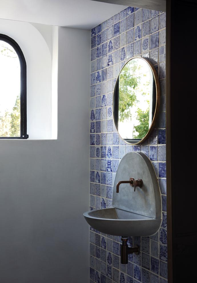 Arches are repeated in the various rooms, as in this guest bathroom. Tracy commissioned Ceramic Matters to make the hand-painted tiles. The concrete washbasin by StoneCast offers an alternative to the typical porcelain basin.