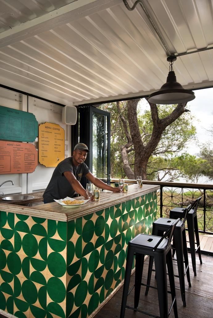 Robert Kelosas in the upstairs bar. The bar counter was made by printing a modern graphic print in green onto wood so it looks like it has been clad in wooden tiles.