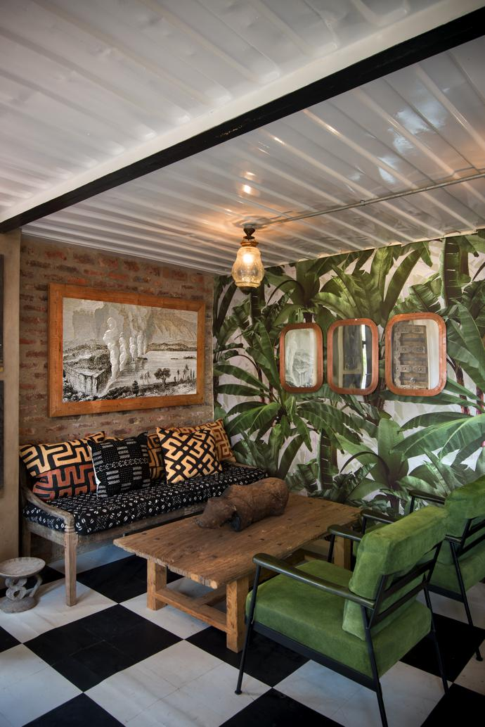 The wallcovering in this nook is a design by Franco Moz for Robin Sprong Wallpaper, called Crazy Banana Camo. The mirrors in copper frames are from Amatuli, as are the green chairs, from the Hausa range. The artwork is a reproduction of a Vic Falls etching from Shutterstock, and the ceiling light comes from India. On the sofa are mud and Kuba cloth cushions, and the warthog was bought from a Zimbabwean trader.