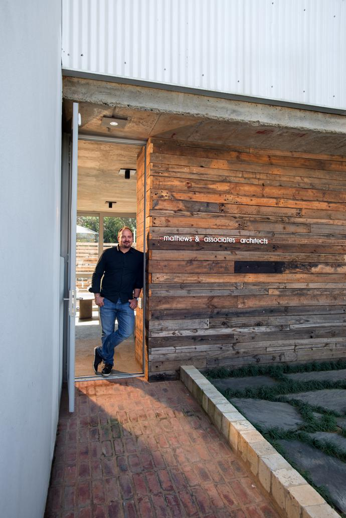 Architect Pieter Mathews, leaning against the wall clad in timber that was originally used for the roof trusses.