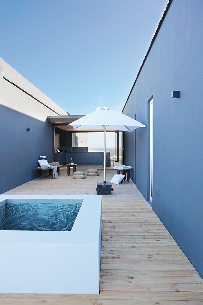 The square raised plunge pool is protected by the wind on the deck that looks out on the fynbos green belt at the back of the property.