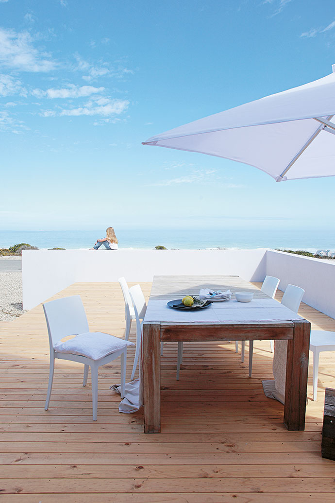 The house is located just across the road from the sea. The curve of the coastline offers a panoramic sea view. The Elsners chose simple, durable materials that could withstand the coastal conditions, such as aluminium window frames, frameless stacking doors and pine decking. The table is from Weylandts and the chairs are from Builders Warehouse.
