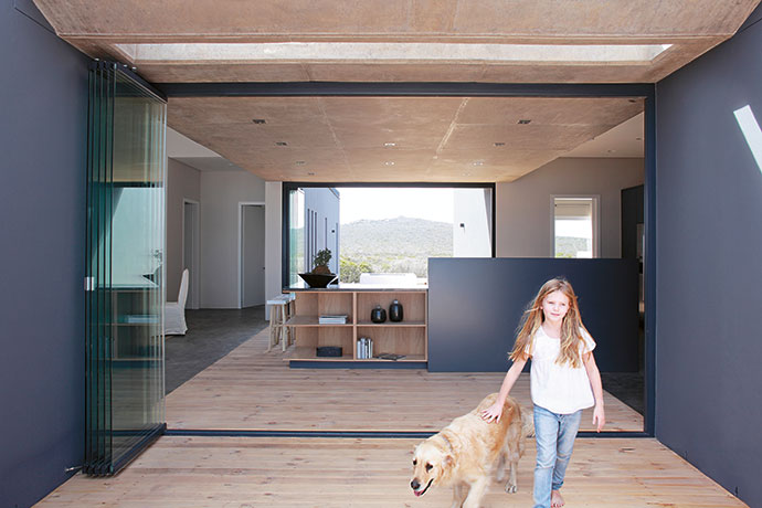 The kitchen is flanked by the two outdoor entertainment areas – the fynbos-facing one is visible in the background. Frameless glass stacking doors and decking that runs from inside to outside assists in breaking down interior-exterior barriers.