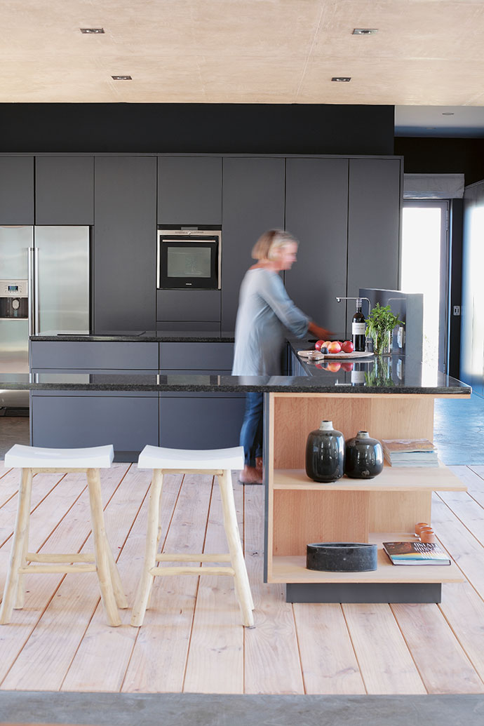 Evi at work in the contemporary kitchen designed by Home Concept and created by A Husband's Hands. The cabinetry was matched to the dark grey colour used elsewhere in the house. The carved bar stools are from Weylandts.