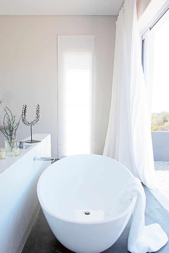 The passage leads to the main bedroom, which features a freestanding bath that looks out on fynbos.