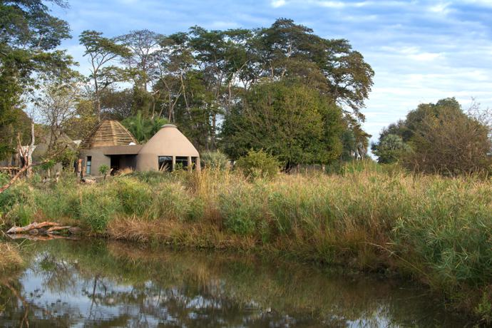 The spa and gym, housed in domed buildings similar to the reception and library, sit harmoniously in the wetland landscape against a backdrop of tall trees on the river bank.