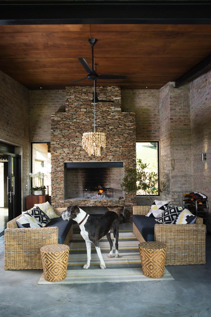 Malibu cane outdoor couches complement the brick and stone-clad braai area, where Judith and Francis love to light a fire. A large rectangular wooden chandelier is suspended from the ceiling. The furnishings and lighting are all from Isabelina.