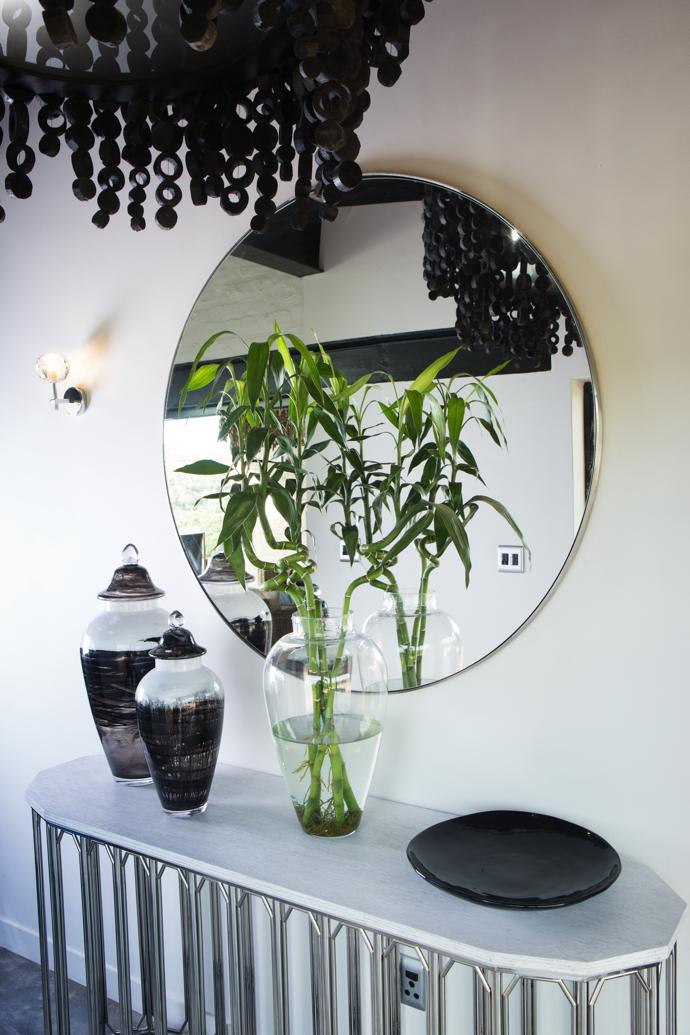 In the hallway, a round mirror with a stainless steel frame reflects natural light; a dark round wooden chandelier adds visual interest; and a Regent console with a chrome base and high gloss white top provides a surface for a display of some of the owners' collectibles. All three pieces are from Isabelina.