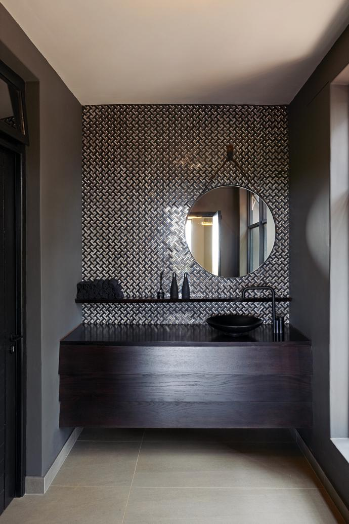 Metallic elements in the bathrooms echo the fireplace surround and bar, and contrast with the rough texture of the slate.